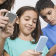 Multi-ethnic siblings looking at cell phones — Stok fotoğraf
