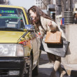 Asian woman talking to taxi cab driver — Stock Photo