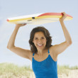 Hispanic woman holding boogie board over head — Stock Photo