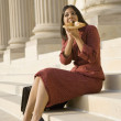 Indian businesswoman eating on steps — Stock Photo