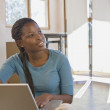 African woman next to laptop in new home — Stock Photo