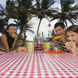 Hispanic family eating at picnic table — Stock Photo