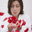 Hispanic woman blowing flower petals — Stock Photo