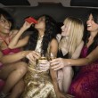 Stock Photo: Multi-ethnic women drinking in limousine