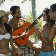 Hispanic man playing guitar for friends — Stock Photo #23314332