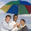 Multi-ethnic businesspeople under beach umbrella — Stock Photo