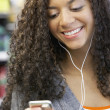 Mixed Race woman listening to mp3 player — Stock Photo