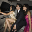 Multi-ethnic friends sitting in limousine — Stock Photo #23314460