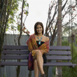 Hispanic woman sitting on bench swing — Stock Photo