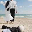 African bride and groom walking on beach — Stock Photo