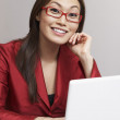 Stock Photo: Asibusinesswomnext to laptop