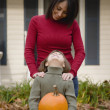 Hispanic mother and daughter holding pumpkin — Stock Photo #23314818