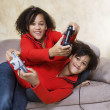 African twin sisters playing video games — Stock Photo #23314926