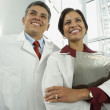 Hispanic male and female doctors with chart — Stock Photo