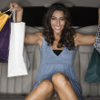 Middle Eastern woman holding shopping bags in limousine — Stockfoto