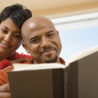 African couple reading same book — Stock Photo