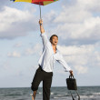 Hispanic businessman holding beach umbrella — Stock Photo