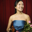 Asian woman holding violin and flowers on stage — Stock Photo