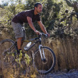 Hispanic man riding mountain bike — Stock Photo #23315180