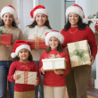 Hispanic family wearing Santa Claus hats and holding gifts — Stock Photo