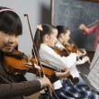 Asian girl playing violin in music class — Stock Photo