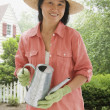 Asian woman holding watering can — Stock Photo