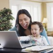 Foto de Stock  : Mixed Race mother and baby looking at laptop