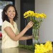 Mixed Race woman arranging flowers — Stock Photo
