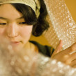 Asian woman pushing aside bubble wrap — Stock Photo