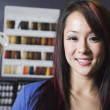 Asian woman in front of hair dye samples — Stock Photo