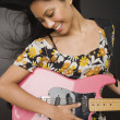 Pacific Islander woman playing electric guitar — Stock Photo
