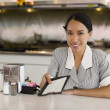 Asian waitress holding out bill — Stock Photo