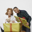 African man surprising girlfriend with puppy — Stock Photo