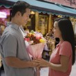 Asian man giving flowers to girlfriend — Stock Photo