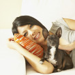 Asian woman and dog laying on sofa — Stock Photo