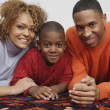 Stock Photo: Africfamily laying on rug