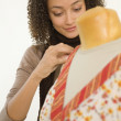 African woman pinning fabric on dress dummy — Stock Photo