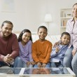 Mixed Race family sitting on sofa — Stock Photo