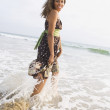 African woman wading in ocean surf — Stock Photo