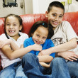 Asian siblings tickling sister — Stock Photo