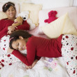African twin sisters laying on bed — Stock Photo