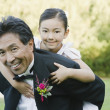 Asian father giving daughter piggy back ride — Stock Photo