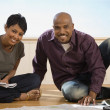 African couple sitting on floor — Stock Photo