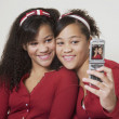 African twin sisters taking own photograph — Lizenzfreies Foto