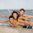 Hispanic family laying on beach — Stok fotoğraf