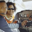 African couple in cockpit of airplane — Stock Photo