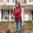 Hispanic woman raking leaves — Stock Photo