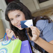 Hispanic woman holding credit card and shopping bags — Stock Photo
