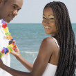 African woman touching lei around husband's neck — Stock Photo