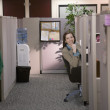 Stock Photo: Hispanic businesswomlooking out from cubicle